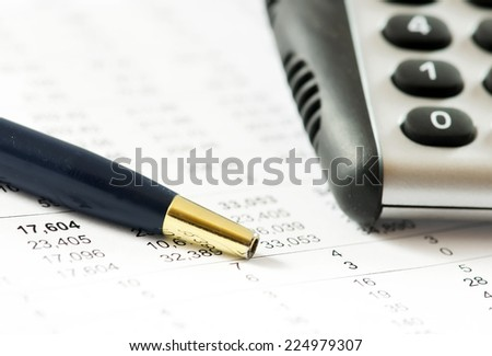 Calculator and pencil on a financial report. - stock photo