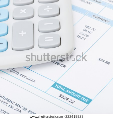 Calculator and utility bill - 1 to 1 ratio - stock photo