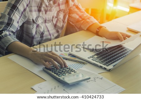 Calculator, business owners, employees,analyze the results,business,people, accounting and technology,businessman,laptop computer, calculator and papers working in office,selective focus,vintage color - stock photo