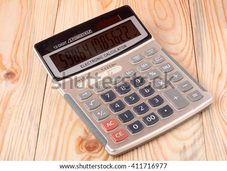 calculator close up isolated on a light wooden background - stock photo