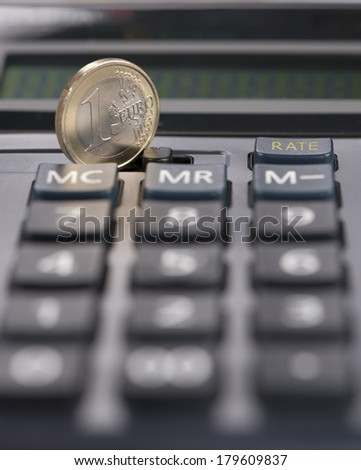 Calculator digits with euro coin standing. Financial crisis is widely spread across the EU.  - stock photo
