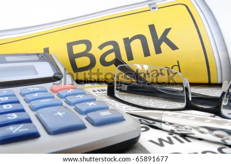 """Calculator, glasses and ball point in front of the lettering """"Bank"""" - stock photo"""