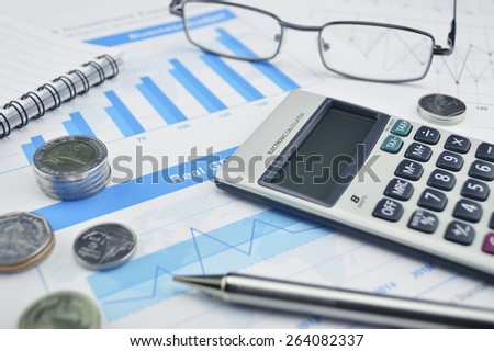 Calculator glasses and pen on financial chart and graph, accounting background - stock photo