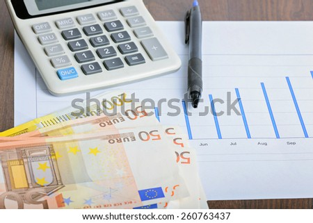 Calculator, graphyc and pen on the table - stock photo