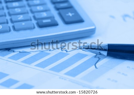 Calculator in background. Pen is focus on stock graphs - stock photo