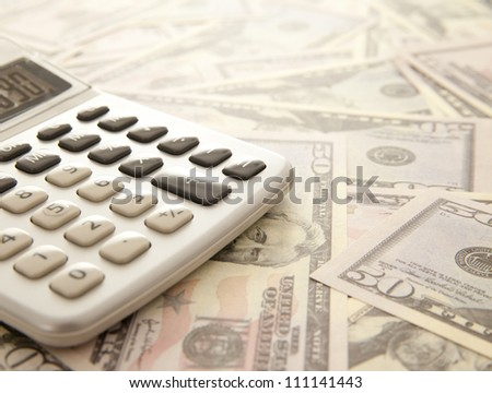 Calculator on a dollars background - stock photo