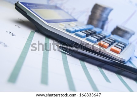 calculator on graph paper and coins - stock photo