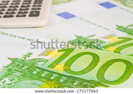 calculator on several euros banknotes - stock photo