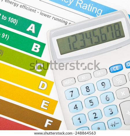 Calculator over energy efficiency chart - studio shot - stock photo