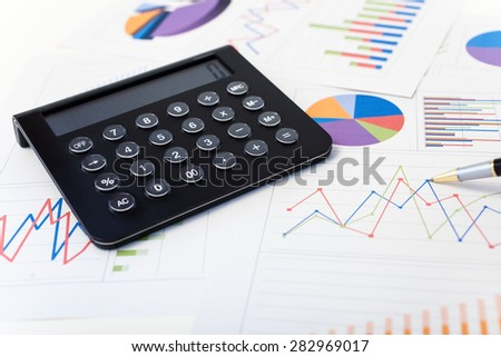 Calculator over financial charts - stock photo