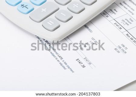 Calculator over utility bill - stock photo