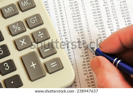 Calculator, pen and a table with figures - stock photo