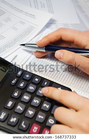 Calculator, pen and accounting document with a lot of numbers and woman hands  - stock photo