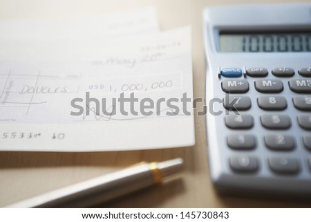 Calculator; pen and filled cheque on wooden table - stock photo