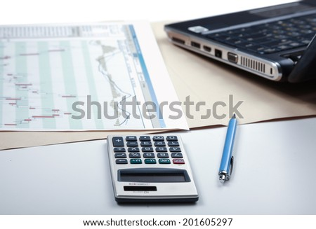 Calculator, pen,laptop, document lying on the desk - stock photo