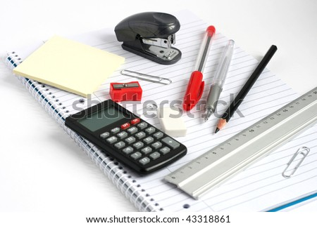 calculator pens pencil ruler and stapler on white lined notepad - stock photo