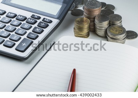 Calculator, red pen, Thai coin stack and notebook - stock photo