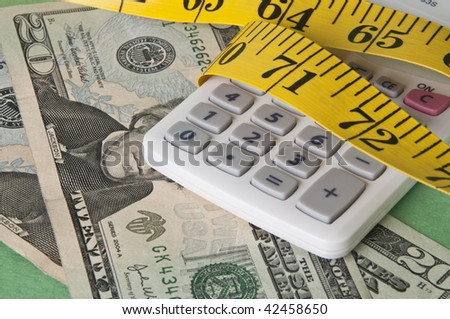 Calculator squeezed by a measuring tape representing a tight holiday budget. - stock photo
