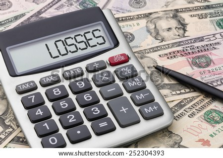 Calculator with money - Losses - stock photo