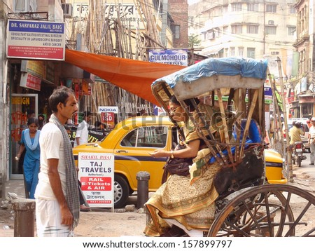 CALCUTTA - SEPTEMBER 12: rickshaw driver waits for customer payment in Calcutta, September 2008. Rickshaws have been around for more than a century, but they could soon be a thing of the past. - stock photo
