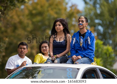 CALDWELL, IDAHO/USA - SEPTEMBER 27:Four unidentified students sitting on the top of a car at the Caldwell High School Homecoming parade on September 27, 2013  - stock photo