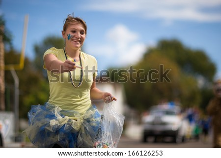 CALDWELL, IDAHO/USA - SEPTEMBER 27: Student passing out candy to the crowd at the Caldwell High School Homecoming parade on September 27, 2013  - stock photo