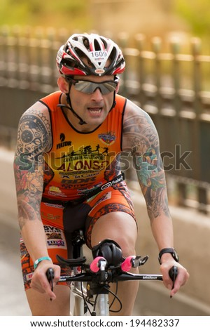CALELLA, SPAIN MAY 18:  Triathlete rides speed cycle on the Ironman triathlon competition at Calella beach, May 18, 2014 in Calella, Spain - stock photo