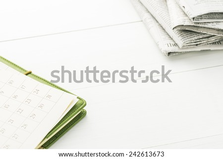 Calendar and Newspaper.Office supply on Blank Desk. - stock photo