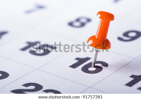 Calendar close-up view with red pin on date - stock photo
