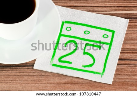 Calendar on a napkin and cup of coffee - stock photo