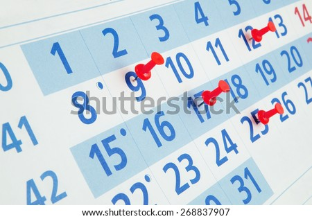 Calendar page with push pins close up - stock photo