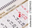 Calendar page with red thumbtack on February 14 2014. Closeup. - stock photo