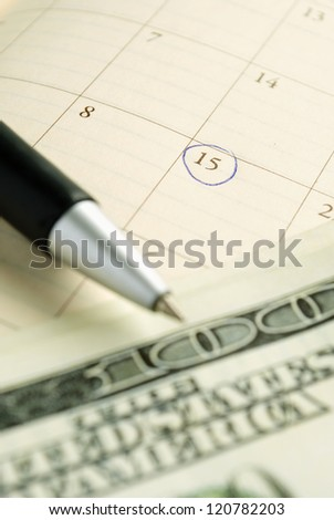 calendar, pen and dollars on the table - stock photo