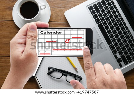 Calender Planner Organization Management Remind message on hand holding to touch a phone, top view, table computer coffee and book - stock photo