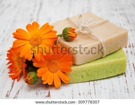 Calendula and handmade soap on a wooden background - stock photo