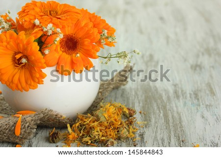 Calendula flowers in vase on wooden background - stock photo