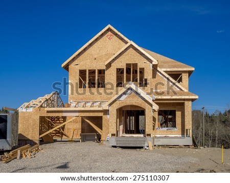 CALGARY, CANADA - APRIL 26: Suburban estate home under construction in Aspen Woods on April 26, 2015 in Calgary, Alberta. In the framing stage, this home is typical of upscale Calgary suburbs. - stock photo