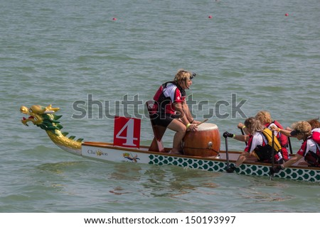 CALGARY, CANADA - AUGUST 11: Dragon Boat team works together in the annual Calgary Dragon Boat Race & Festival on 11 August 2013 at North Glenmore Park in Calgary. - stock photo