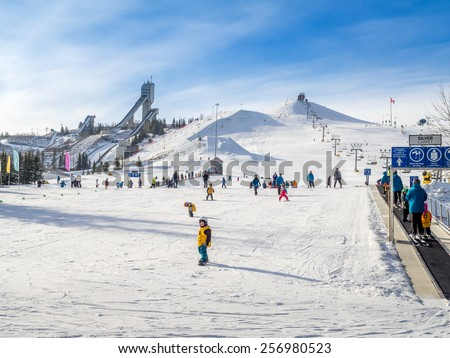 CALGARY, CANADA - MAR 1: People enjoying the skiing at  Canada Olympic Park on March 1, 2015 in Calgary, Alberta.  Visible are skiers at the base of the hill. Ski jump towers are on the top left.   - stock photo