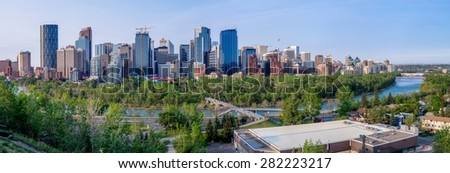 CALGARY, CANADA - MAY 24: Calgary's skyline with the Bow River in the foreground May 24, 2015. The Peace Bridge is visible on the far right and the Bow Tower on the far left. - stock photo