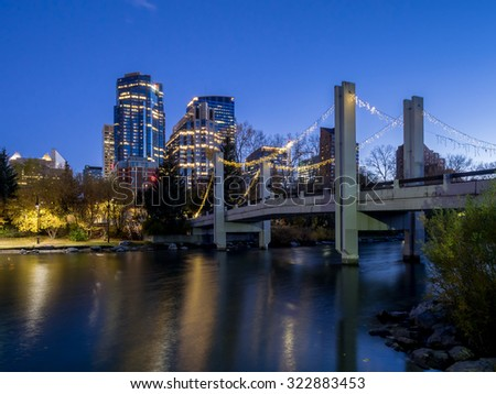 CALGARY, CANADA - SEPT 26: Skyscrapers tower over urban park space along the Bow River in the city of Calgary on September 26, 2015. The park is in the Eau Claire district of Calgary's urban centre. - stock photo