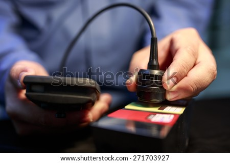 Calibration paint coating thickness tester with plastic shim  - stock photo