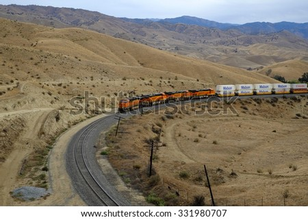 CALIENTE, CA - OCT 25, 2015: A westbound BNSF freight train, pulled by diesel-electric engines, slowly descends out of the Sierra Nevada Range. It's about to enter one of many tunnels along the route. - stock photo