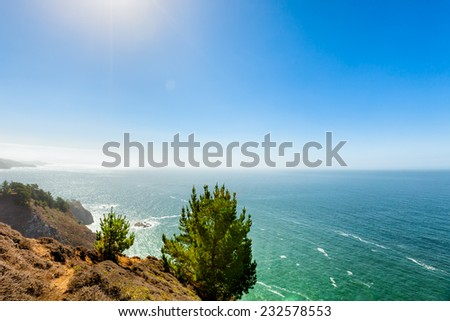 California coastal trail on a cliff overlooking the Pacific Ocean. Natural sun flare in a blue sky. Location: About 30 miles north of San Francisco. Copy space. - stock photo