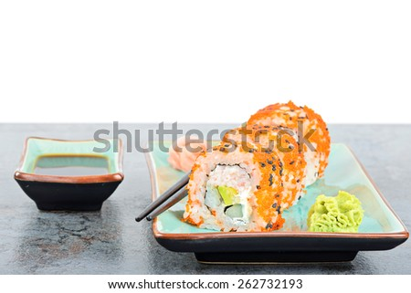 California maki sushi with masago on the table. Roll made of crab meat, avocado, cucumber and masago. - stock photo