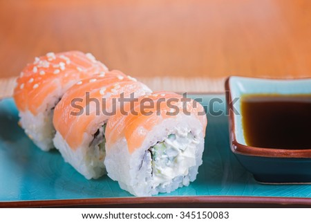 California maki sushi with salmon. Roll made of salmon, cream cheese and  cucumber. Shallow depth of field.  - stock photo