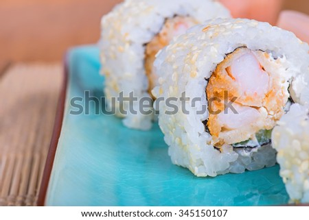 California maki sushi with tempura shrimp. Roll made of tempura shrimp, cream cheese, sesame and  cucumber. Shallow depth of field.  - stock photo
