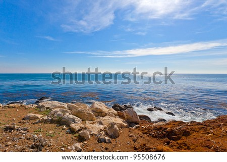 California ocean, blue sky and a colorful rocky beach on a sunny day - stock photo
