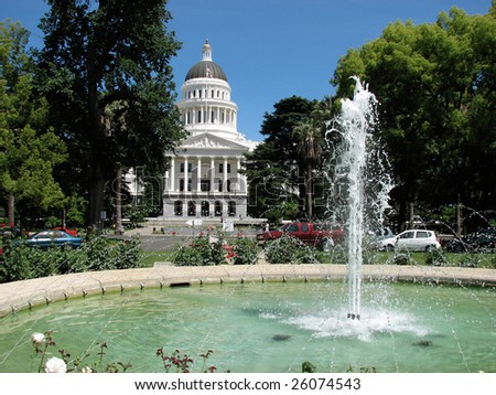 California State Capital in Sacramento on a perfect day with green trees and blue sky framing the white building through a fountain - stock photo