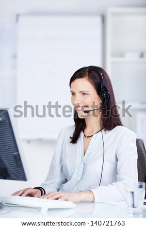 Call center agent working in front of her computer - stock photo
